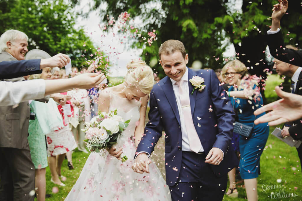 Guests throwing lots of confetti at the Bride and Groom outside